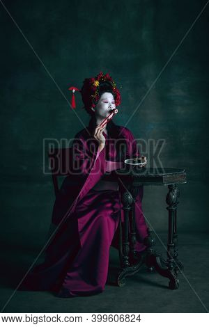 Eating Sushi. Young Japanese Woman As Geisha Isolated On Dark Green Background. Retro Style, Compari