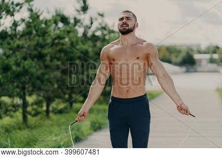 Athletic Motivated Man With Naked Torso Concentrated On Intense Fitness Training Program Jumps Over