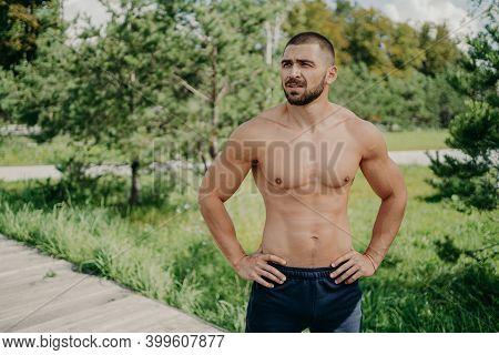Horizontal Shot Of Thoughtful Shirtless Sportsman Keeps Hands On Waist, Looks Away Demonstrates His