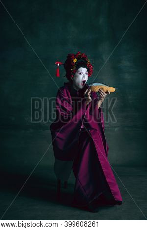 No Diet With Hot-dog. Young Japanese Woman As Geisha Isolated On Dark Green Background. Retro Style,