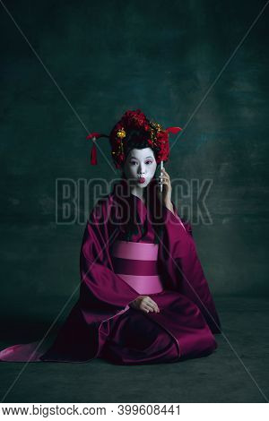 Talking Phone. Young Japanese Woman As Geisha Isolated On Dark Green Background. Retro Style, Compar