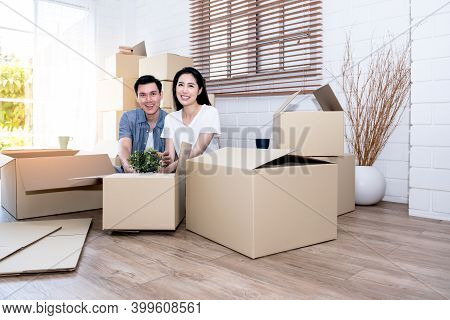 Asian Couple, Husband And Attractive Wife Are Happiness And Are Helping Each Other Lose Things Into