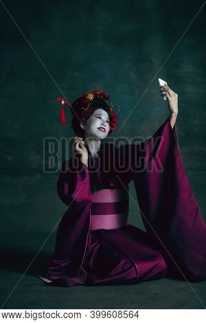 Vlog, Blog. Young Japanese Woman As Geisha Isolated On Dark Green Background. Retro Style, Compariso