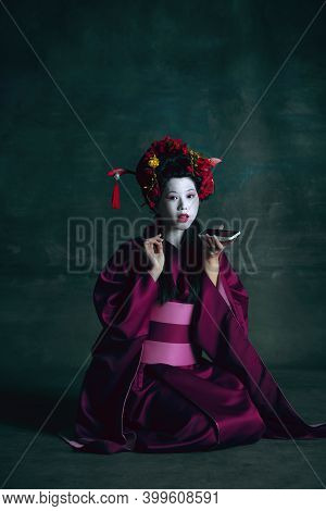Voice Message. Young Japanese Woman As Geisha Isolated On Dark Green Background. Retro Style, Compar
