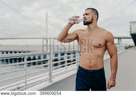Active Sportsman Drinks Bottle Of Water Poses With Naked Torso Concentrated Into Distance Feels Thir