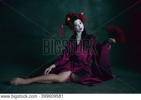Passioned. Young Japanese Woman As Geisha Isolated On Dark Green Background. Retro Style, Comparison