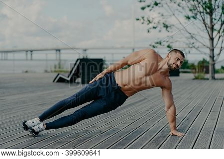 Sporty Bodybuilder Stands In Side Plank, Exercises Outdoor And Wears Sport Clothes, Leads Healthy Li