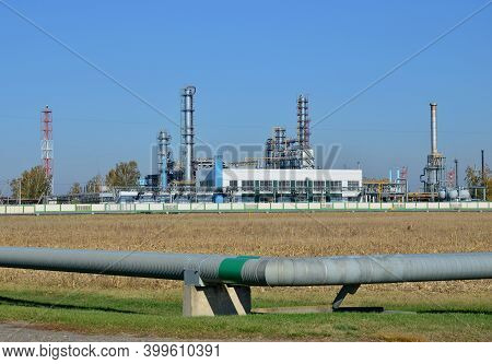 Gas Processing Plant. Power Pipes And Industrial Refinery Towers Of Natural Gas Factory On The Backg