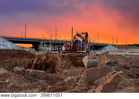 Excavator During Excavation At Construction Site On Amazing Sunset Background. Backhoe On Road Work.