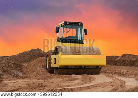 Vibration Single-cylinder Road Roller On Amazing Sunset Background. Soil Compactor For Leveling Grou