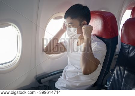 A Travelling Man Is Wearing Protective Mask Onboard In The Aircraft, Travel Under Covid-19 Pandemic,