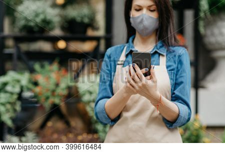 Small Business, New Normal, Online Media And Social Distancing. Millennial Woman In Apron And Face S