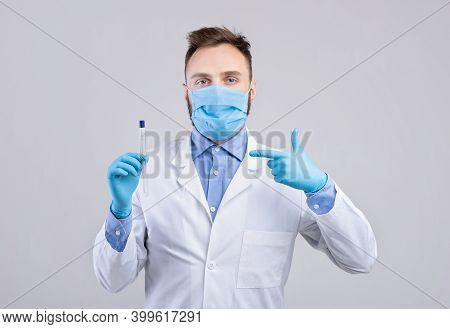 Male Doctor Wearing Protective Mask And Gloves, Pointing At Coronavirus Pcr Test Tube On Grey Studio