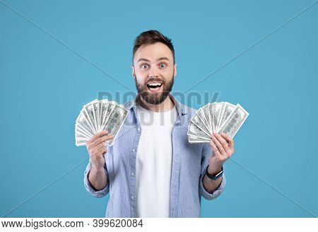 Excited Millennial Guy Holding Fan Of Money Banknotes Over Blue Studio Background. Funky Caucasian M