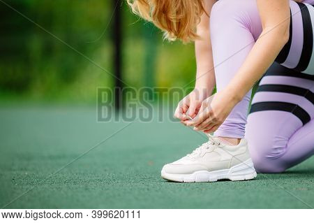Cropped Image Of Hands Tying Shoelaces Of Sneaker. Young Woman Runner Tying Shoelaces