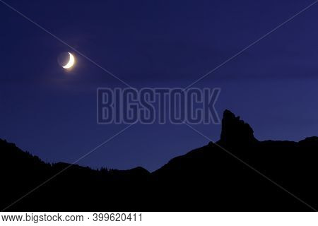Silhouette Of A Mountain Landscape Under A Blue Magenta Sky With A Bright Sickle (crescent) Moon Dur