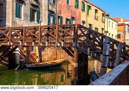 Venice, Italy. Boat Moored In The Narrow Canal Under The Wooden Bridge