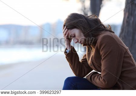 Profile Of A Sad Woman Complaining Sitting On A Bench In Winter On The Beach