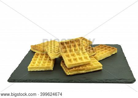 Delicious Waffles On A Stone Board On A White Background. Waffles Sprinkled With Powdered Sugar Lie