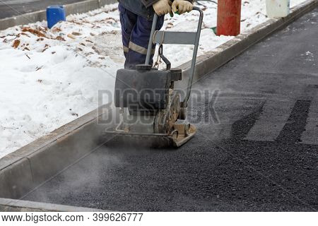 Worker Use Vibratory Plate Compactor For Ramming Asphalt. Men At Work. Laying New Asphalt Pavement O