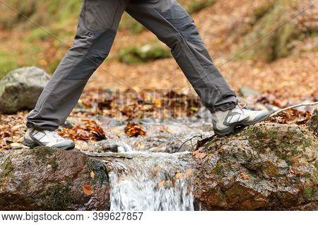 Side View Close Up Of A Trekker Legs Walking Crossing A River In Winter