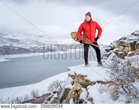 senior man with classic Huron snowshoes is overlooking a mountain lake in winter scenery - Horsetooth Reservoir in northern Colorado