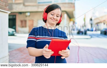 Beautiful brunette woman with down syndrome at the town on a sunny day using touchpad device listening to music wearing headphones