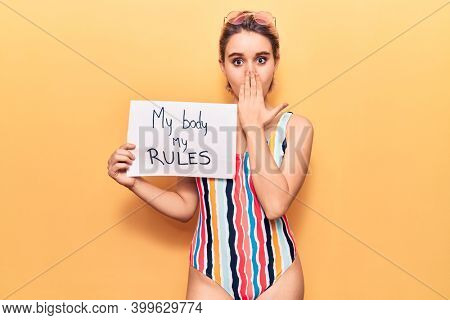 Young beautiful blonde woman wearing swimwear holding my body my rules banner covering mouth with hand, shocked and afraid for mistake. surprised expression