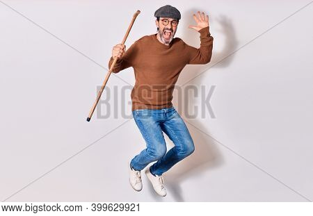 Senior elderly man  wearing beret and glasses smiling happy. Jumping with smile on face holding walking stick over isolated white background