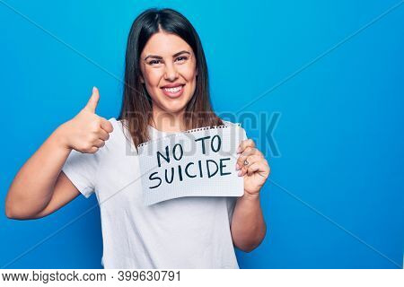 Young beautiful woman asking for psychical problem holding paper with not to suicide message smiling happy and positive, thumb up doing excellent and approval sign