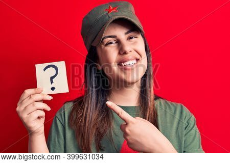 Beautiful woman wearing cap with red star communist symbol holding question mark reminder smiling happy pointing with hand and finger