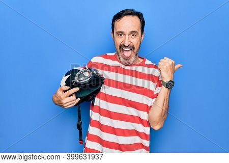 Middle age handsome motorcyclist man holding moto helmet over isolated blue background pointing thumb up to the side smiling happy with open mouth