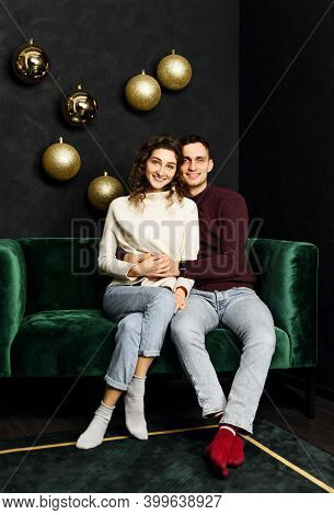 Guy Hugs A Girl While Sitting On The Couch In Christmas Clothes. The Wall Is Decorated With Garlands