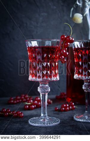 Beautiful Glass Goblet With Red Currant Alcohol Drink, Bunch Of Currants On A Glass. Bottle With Red