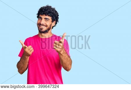 Handsome young man with curly hair and bear wearing casual pink tshirt pointing fingers to camera with happy and funny face. good energy and vibes.