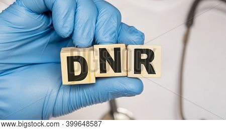 Dnr Do Not Resuscitate - Word From Wooden Blocks With Letters Holding By A Doctors Hands In Medical