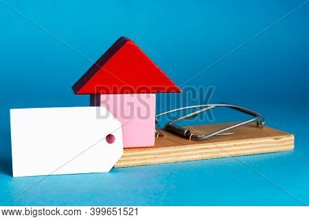 Blank White Tag And A Small House In A Mousetrap. Real Estate Insurance. Investment In Real Estate.