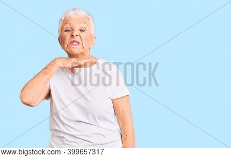 Senior beautiful woman with blue eyes and grey hair wearing casual white tshirt cutting throat with hand as knife, threaten aggression with furious violence