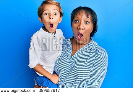 Hispanic family of mother and son hugging together with love scared and amazed with open mouth for surprise, disbelief face