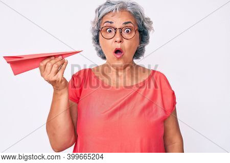 Senior hispanic grey- haired woman holding paper airplane scared and amazed with open mouth for surprise, disbelief face