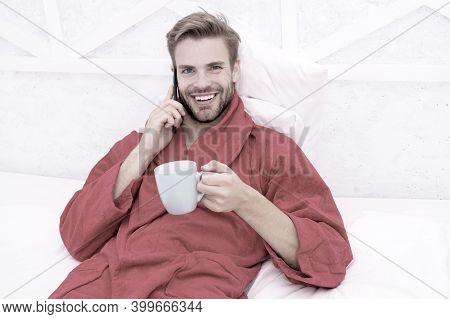 Break Time. Happy Guy In Bathrobe Relaxing During Break In Bed. Handsome Man Talking On Mobile Phone