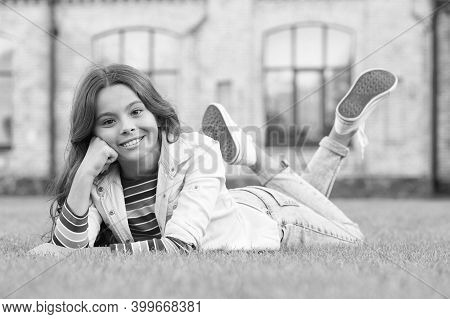A Look Of Perfection. Happy Girl Rest On Grass Outdoors. Beauty Look Of Little Child. Vogue Look. Ca