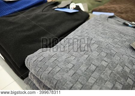Men Knitted Sweaters In Pastel Colors Stacked On Store Counter