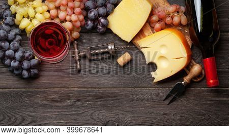 Various grapes, glass of red wine, cheese and wine bottle. Top view flat lay with copy space