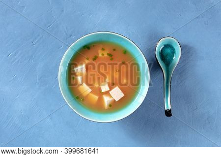 Miso Soup With Tofu And Green Onions, Shot From The Top On A Blue Background