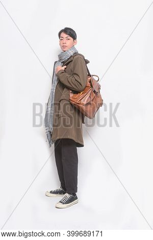Full length portrait of young man in fashion coat, scarf and brow n backpack with black jeans with white sneakers