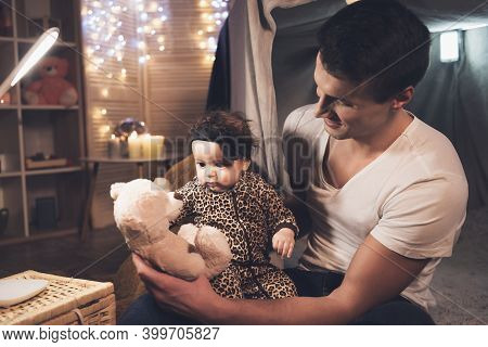 Father Is Playing With Little Baby Daughter At Night At Home.