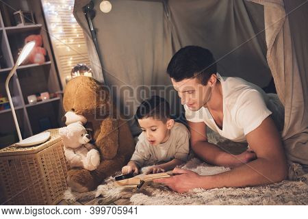 Father And Son Are Reading Book With Magnifying Glass At Night At Home.