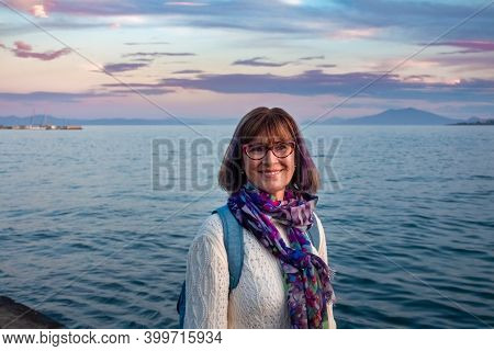 Cheerful Mature Woman With Spectacles Wearing White Sweater And Colorful Scarf Smiling Near The Sea