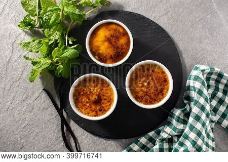 Homemade Creme Brulee In Bowl On Gray Stone Background. Top View
